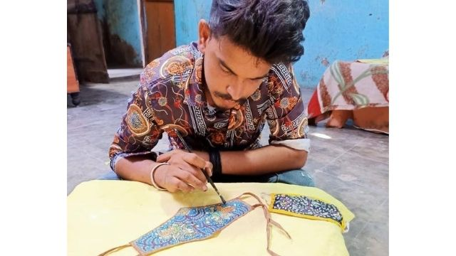 Artisan doing hand made embroidery on double layered cotton masks